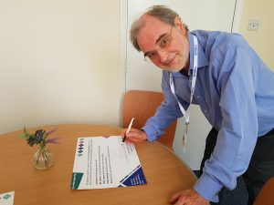 David N Jones, Chair of Healthwatch Northamptonshire, signing the wellbeing pledge