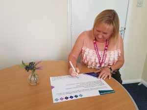 Kate Holt, CEO of Healthwatch Northamptonshire and Connected Together, signing the wellbeing pledge